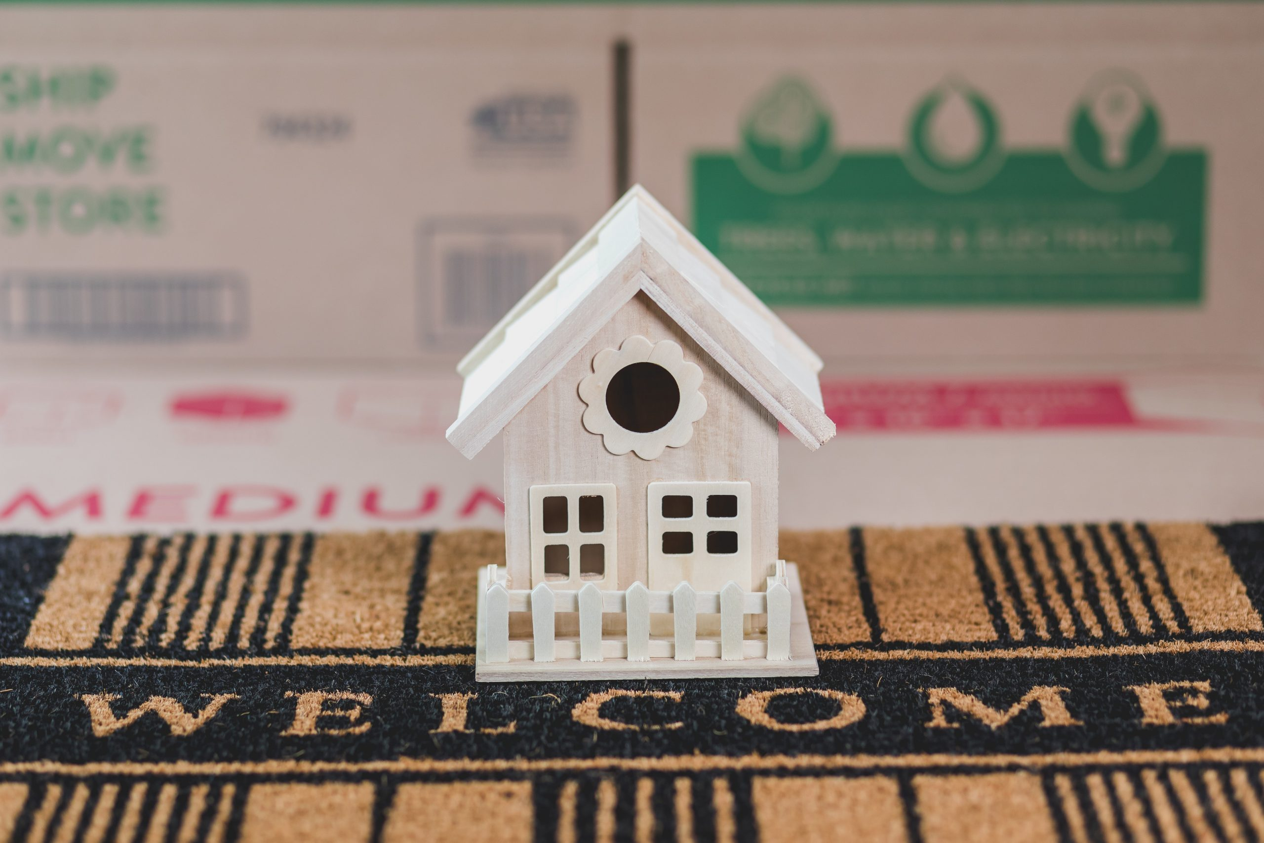 A model of a house positioned on a doormat.